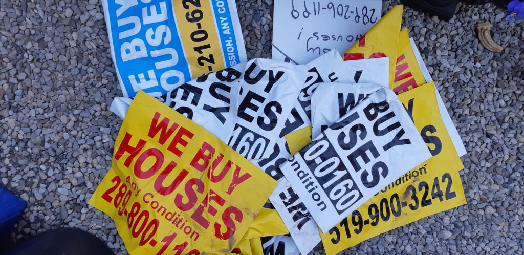 """A pile of stickers and signs with """"We Buy Houses"""" and different phone numbers."""