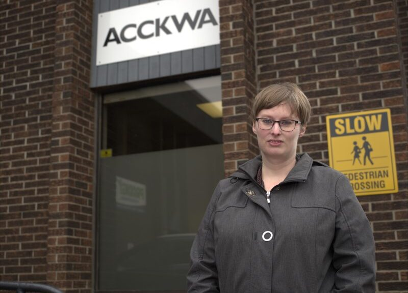"Amy Veener, with glasses and wearing a coat, stands in front of a brown brick building, with a sign reading ""ACCKWA"" in black letter on the white background above a door behind her."