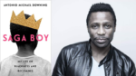 """The cover of the book """"Saga Boy: My Life of Blackness and Becoming"""" with a young black boy with his head looking directly away from the camera, wearing a white tshirt and a golden paper crown tilted on his head. the back ground is white and the text is in black and pink."""
