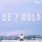 Be/Hold (JSP squatting in the foreground, urban horizon in the background)