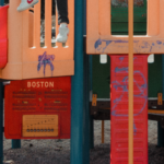 (closeup of playground equipment with a musical instrument labelled Boston)