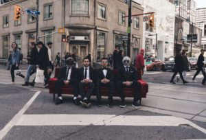 Four people sitting on a couch in the intersection of Dundas and Yonge Streets in Toronto