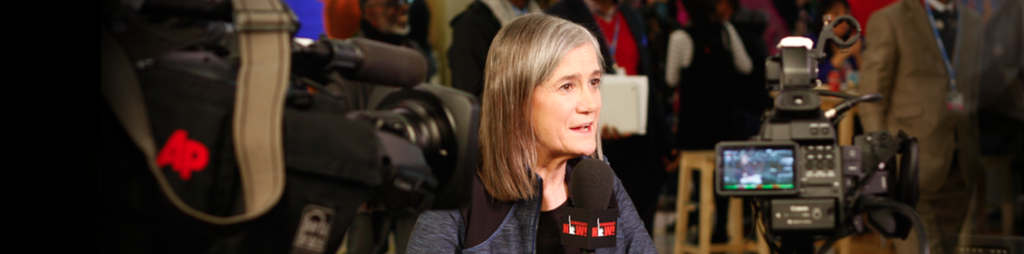 (Amy Goodman at the mic at a press conference surrounded by cameras)