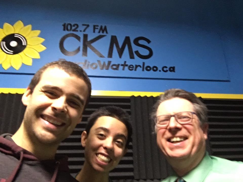 "Keenan Reimer-Watts, Veda Hingert-McDonald and Bob Jonkman under a sign ""102.7 FM CKMS RadioWaterloo.ca"""