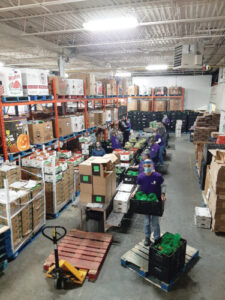 A picture of the food bank warehouse. Boxes and shelving and skids, and hand-carts, fluorescent lights, and even a few volunteers are in this busy colourful picture.