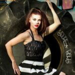 (Ginger St. James in front of a large tractor tire)