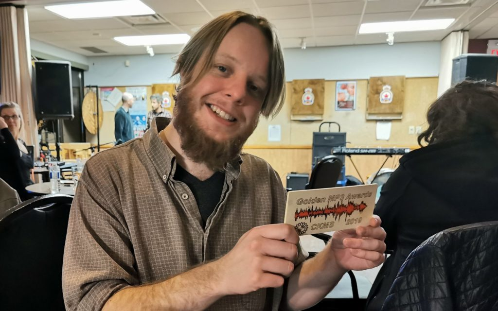 Riley Powis holds his Golden MP3 plaque