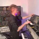 (Sam Battle adjusting settings on an analog syntheszer)