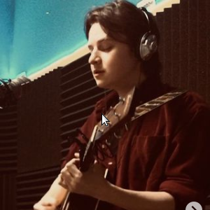 Jake Feeney playing guitar in the CKMS-FM studio
