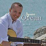 Juneyt | Ocean (Juneyt holding a guitar sitting at the oceanside)