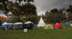 """A picture of O:se Kenhionhata:tie/Land back Camp in Victoria Park in Kitchener. Several tents form a circle around a white tee-pee. A black banner hanging on a tent reads """"reconciliation is dead"""" in white text."""