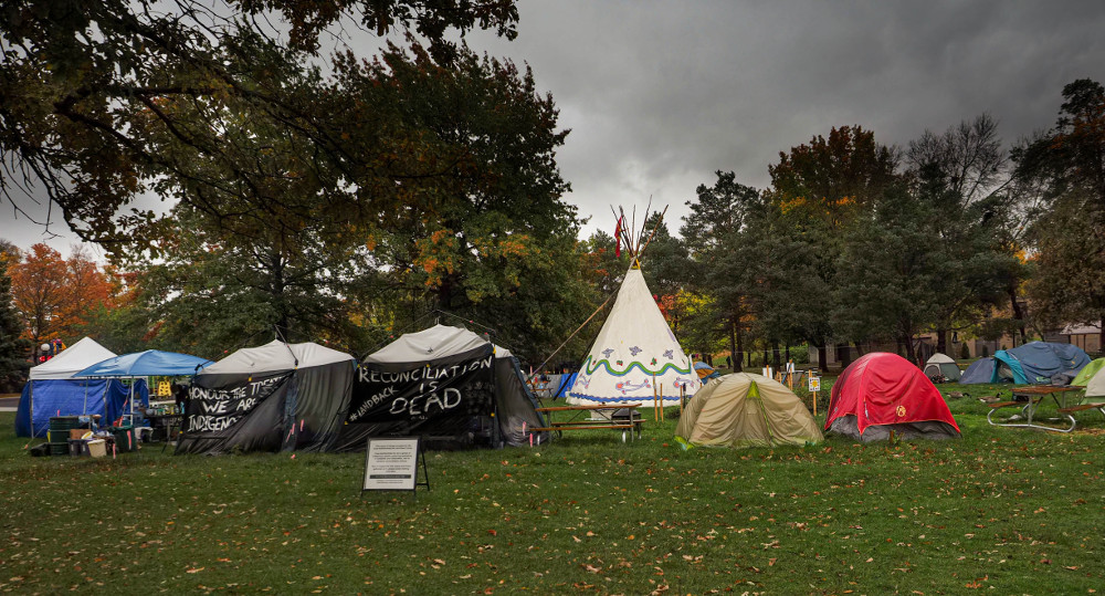 "A picture of O:se Kenhionhata:tie/Land back Camp in Victoria Park in Kitchener. Several tents form a circle around a white tee-pee. A black banner hanging on a tent reads ""reconciliation is dead"" in white text."