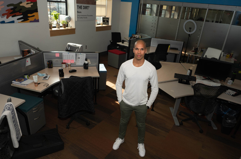 Marc Lafleur, wearing a white shirt and black pants, stands in the centre of his office space.