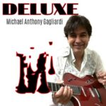 Deluxe | Michael Anthony Gagliardi (Michael Gagliardi holding an electro-acoustic guitar)