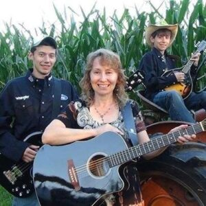 Nelson Family Bluegrass (young men playing instruments on a tractor, Susan Nelson with a guitar in front)
