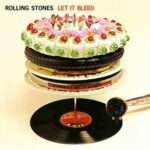 Rolling Stones Let It Bleed (four plastic figures on a cake, on a tire, on a pancake, on a plate, on a film can, all on a record player spindle over a 12 inch vinyl record with a grammophone arm on it)