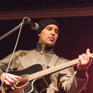 Ryan Fischer playing guitar on stage in front of a microphone