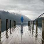 (no text; person standing at the end of a wharf in the rain)