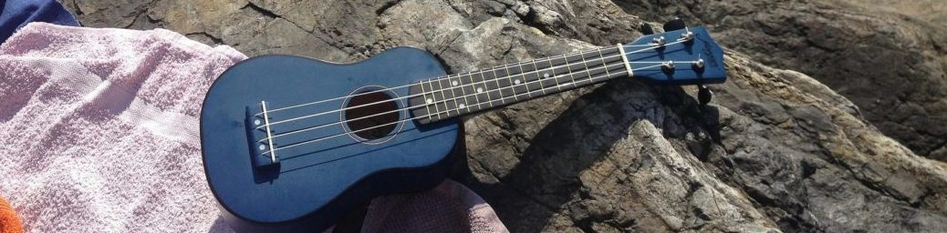 A towel on a rock beside the ocean, with a ukelele on the towel