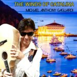 The Winds of Catalina | Michael Anthony Gagliardi (Michael Gagliardi holding a guitar on his shoulder in front of a harbour with sailboats and the Catalina casino in the background)