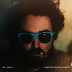 Willy Nilly | Confused and Rejuvenated (portrait of a man's head wearing blue sunglasses and smoking a cigarette)