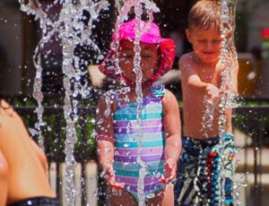 Children play in a water park. Water spouts up as a small girl in a striped pink purple and blue one piece swimsuit and a pink sun hat closely stares and plays. Behind her and on the right on the photo a shirtless bot in blue, white, black and grey Volcom swim trunks catches water from another spout.