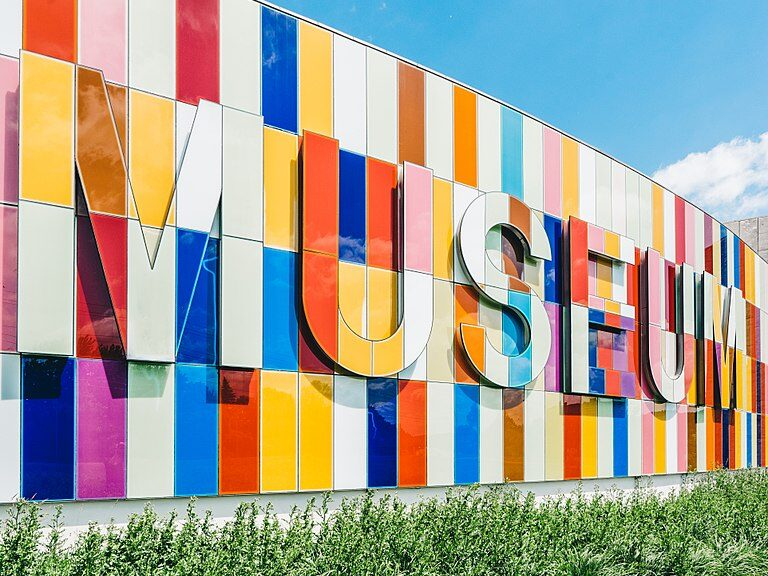 """Picture of the front of the Waterloo Region museum. Greenery and grass at the bottom and blue sky above, the multicoloured wall panels with the word """"MUSEUM"""" in multicoloured panels."""